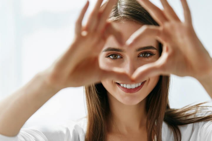 Young girl heart hands around her eyes